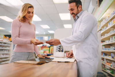 Customer handing a medical prescription to the pharmacist standing behind counter