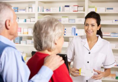 pharmacist dispensing to senior couple smiling