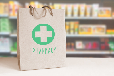 Recycled paper bag with a green Pharmacy logo in a drugstore.