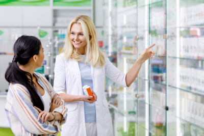 smiling pharmacist holding containers with medication and consulting customer in drugstore